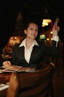 Businesswoman holding credit card and gesturing to waiter