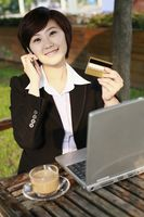 Businesswoman holding credit card while talking on the phone