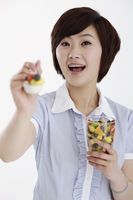 Businesswoman holding out a spoonful of mixed fruits