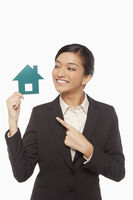 Businesswoman holding up a cut out house