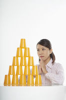 Businesswoman looking at a stack of disposable cups, contemplating