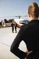 Businesswoman looking at businessmen standing by the helicopter