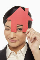 Businesswoman looking through a cut out house