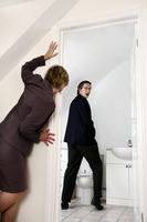 Businesswoman peeping her male colleague in the toilet