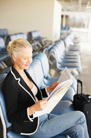 Businesswoman reading newspaper in airport lounge