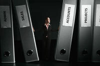 Businesswoman standing in between giant sized files