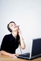 Businesswoman talking on telephone headset and using a laptop