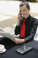 Businesswoman talking on the mobile phone while reading newspaper