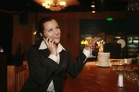 Businesswoman talking on the phone while holding a glass of cocktail