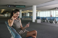 Businesswoman text messaging on phone in airport lounge