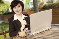 Businesswoman using laptop at an outdoor cafe