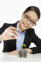 Businesswoman with a test tube and a plant