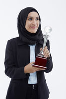Businesswoman with a winning trophy, smiling