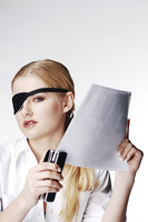 Businesswoman with eye patch stapling papers
