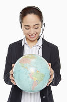 Businesswoman with headset holding a globe