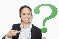 Businesswoman with headset holding up a question mark symbol