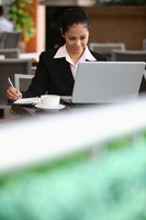 Businesswoman writing on organizer while using laptop