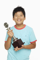 Cheerful boy holding up a trophy