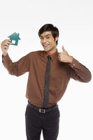 Cheerful businessman holding up a cut out house
