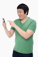 Cheerful man text messaging with his mobile phone