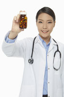 Cheerful medical personnel holding up a bottle of pills