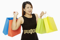 Cheerful woman carrying colorful paper bags