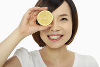 Cheerful woman covering her eye with a lemon