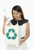 Cheerful woman discarding a plastic bottle into a recycle bin