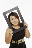 Cheerful woman holding up a black picture frame