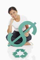 Cheerful woman holding up a dollar sign, with recycle logo placed on floor