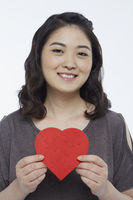 Cheerful woman holding up a red heart shape