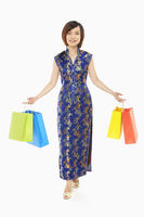 Cheerful woman in traditional clothing carrying paper bags