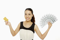 Cheerful woman with a credit card and cash