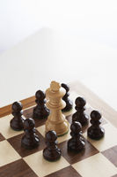 Chess game white king surrounded by black pawns