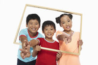 Children holding up a wooden picture frame, smiling