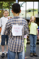 Children laughing at boy with a kick me sign on his back
