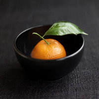Close up of clementine in a black bowl