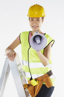 Construction worker standing on a ladder, holding megaphone