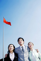 Corporate people standing under a flag