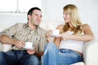 Couple resting on couch enjoying coffee