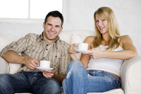 Couple sitting on the couch drinking coffee