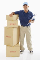 Delivery person standing beside a stack of cardboard boxes