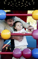 Father and daughter playing with abacus in the playground