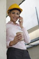 Female architect holding a cup of coffee while talking on the phone