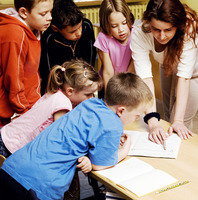 Female teacher pointing at a book with students surrounding her