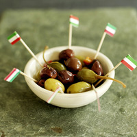 Fresh italian olives in small ceramic bowl with italian flag picks