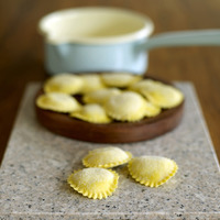 Fresh tortellini pasta on wooden board
