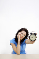 Frustrated woman showing an alarm clock