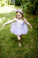 Girl in ballet costume striking dancing in the park