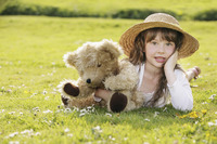 Girl lying on the grass with her teddy bear
